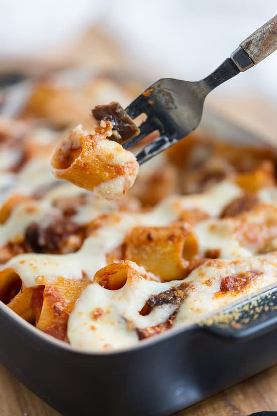 Fork lifting pasta and eggplant bit from casserole.