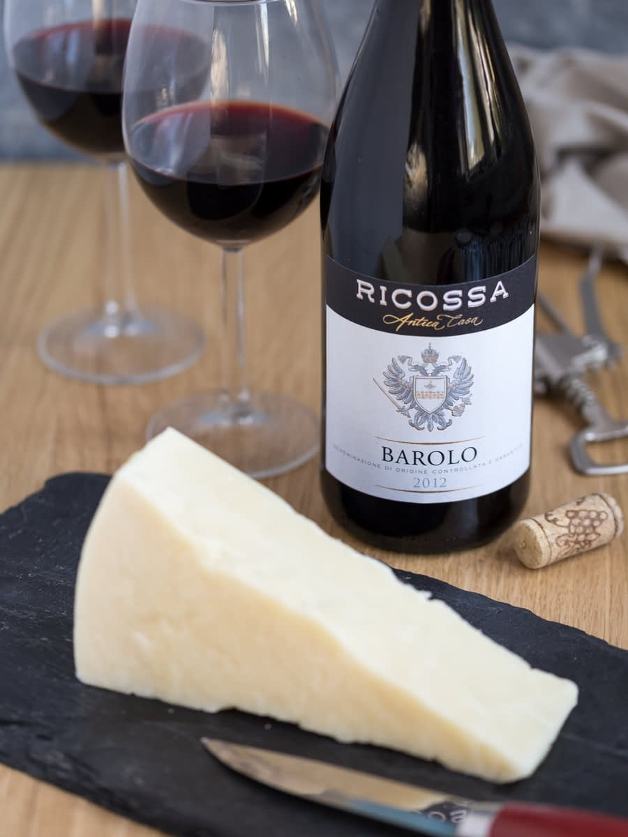 Bottle of Barolo red wine and chunk of Pecorino cheese