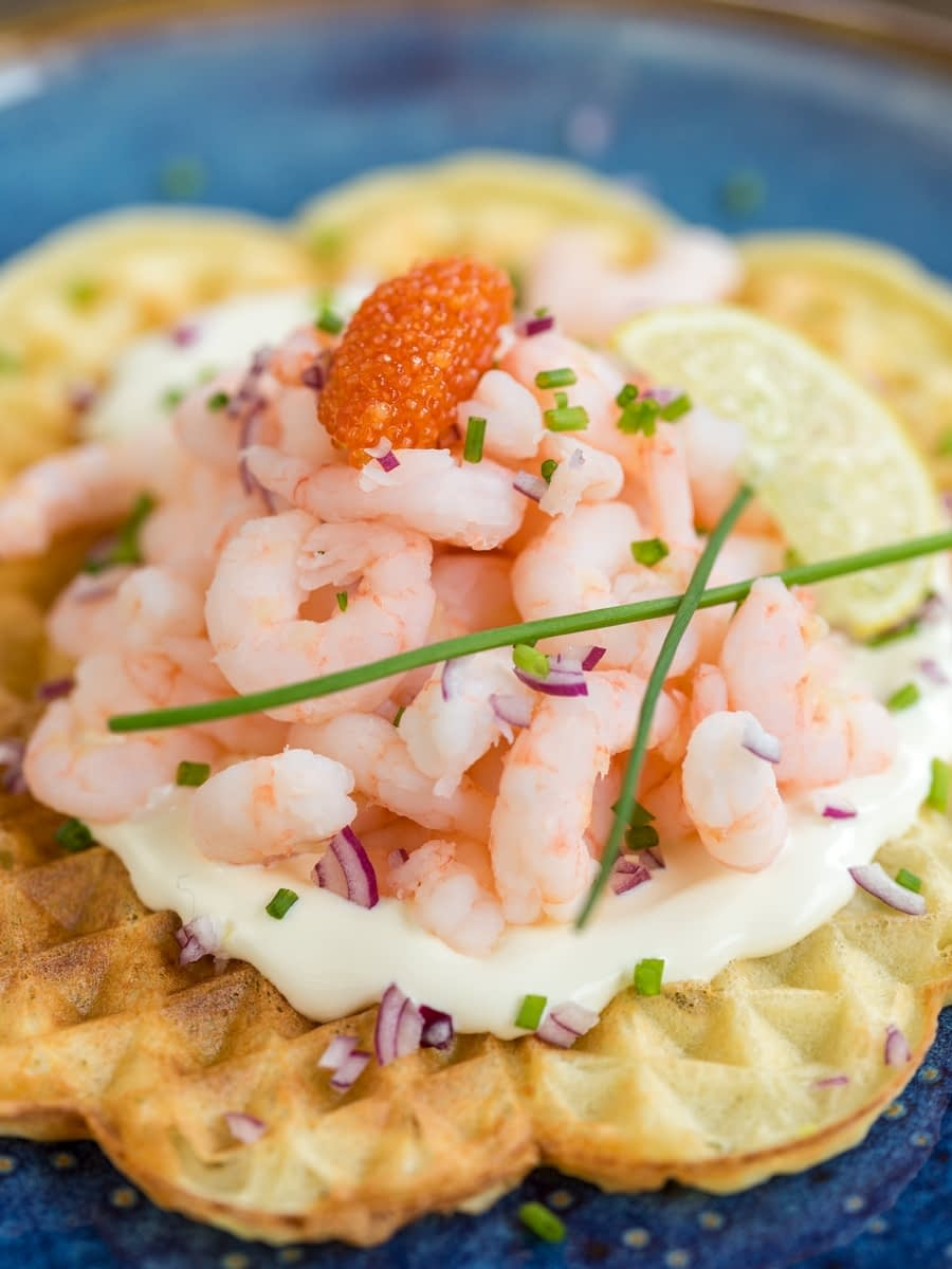 Sour cream waffle with shrimp topping decorated with chives and lemon slice.