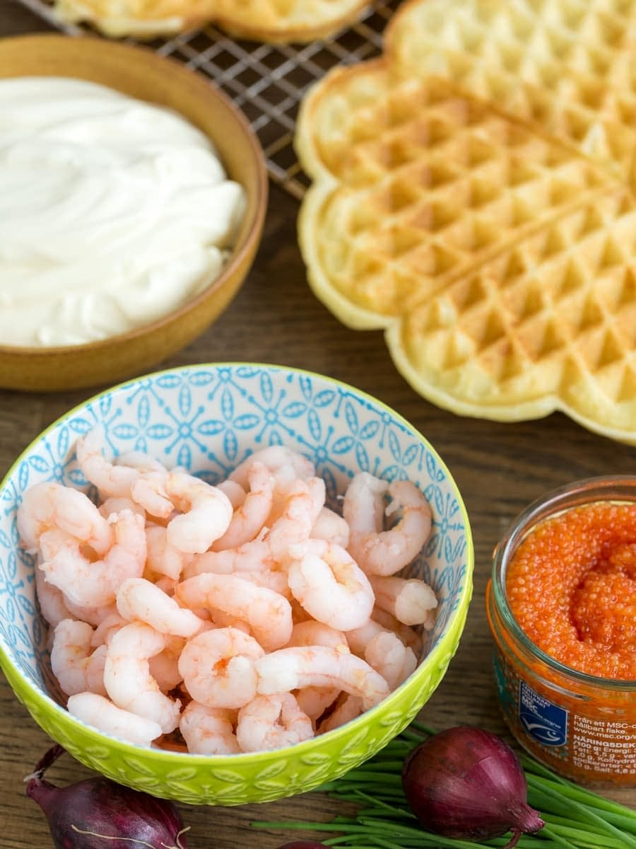 Sour cream waffles with shrimp ingredients: shrimps, roe, creme fraiche, red onion and chives.