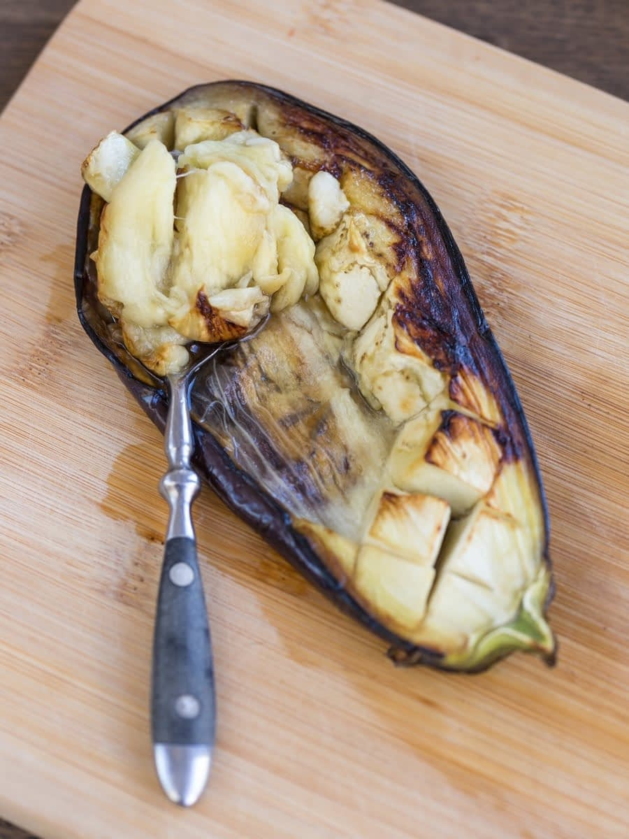 Spoonscooping up baked eggplant flesh.