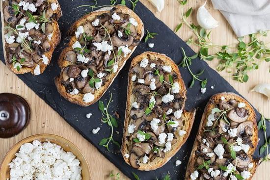 Garlicky mushroom crostini with crumbed goat cheese flat lay.