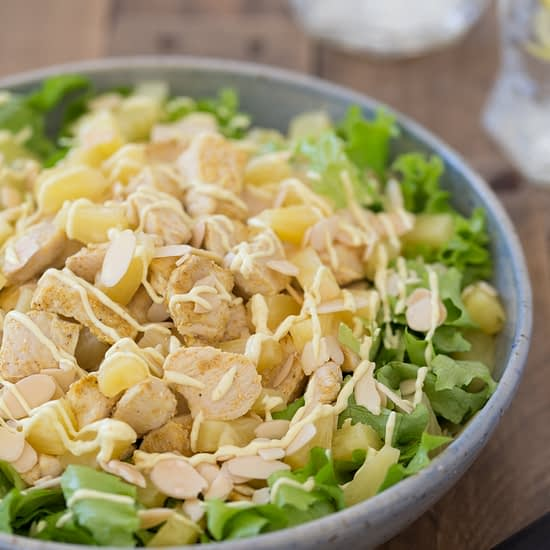 Chicken pineapple salad with curry mayo dressing in a blue bowl.