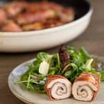 Plated sliced chicken involtini with green salad.
