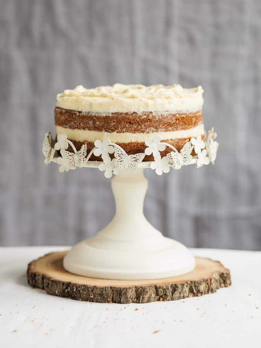 Sweet potato cake with brown butter frosting on white cake stand.