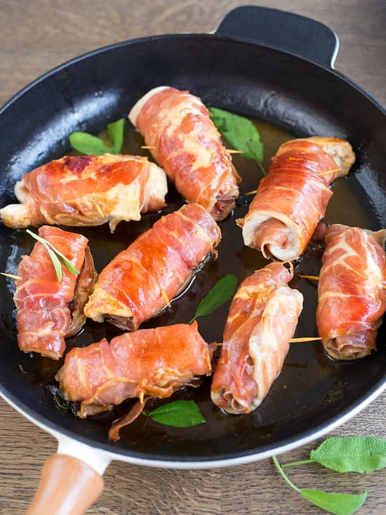 Chicken involtini rolled in prosciutto, cooked in sage butter and white wine in a skillet.