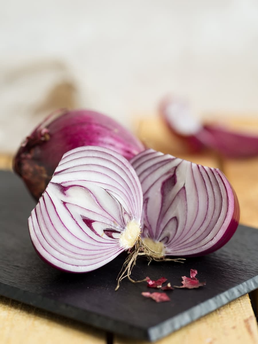Two onions on a cutting board, one is cut in half.